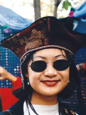 Close up of woman with glasses wearing a red Four Corner Hat.