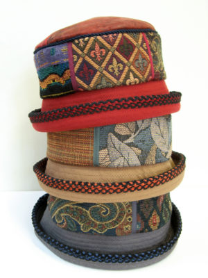 3 Aubery design hats stacked on top of each other grey, beige and red
