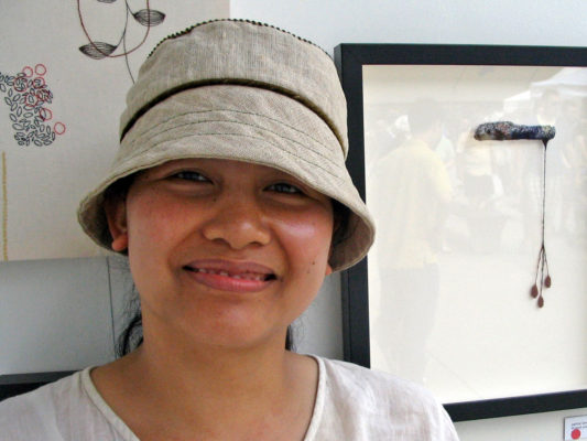 A close up of a woman wearing her new Carval summer hat in front of her artwork at the TOAE