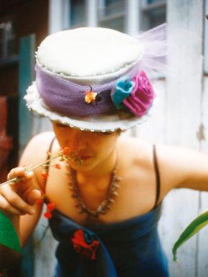 Close up a woman smelling a flower wearing a Bee in the Bonnet hat.