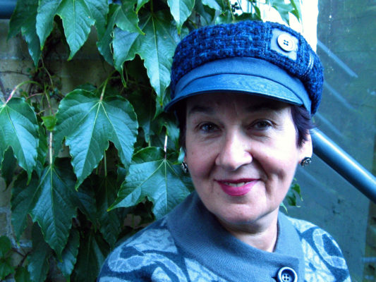 A client wearing a blue Abbey Road cap outside in front of a vine of leaves