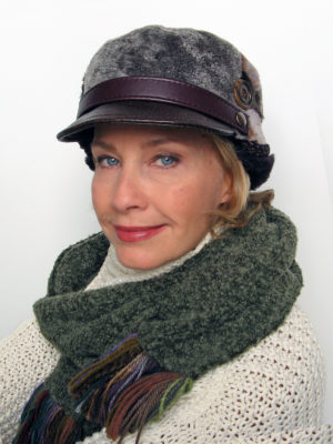Woman wearing a Nadia lamb shearling peaked hat and boucle knit scarf