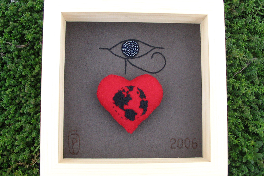 a shadowbox of hand embroidery of Ptah symbol and a felt embroidered heart of the world