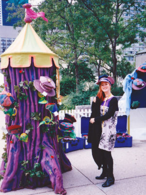 A woman wearing a Gwendolyne Hat beside the big purple display tree of Gwendolyne Hats