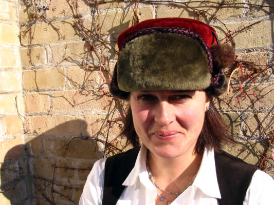 A close up of a woman wearing her new Pom Pom shearling olive green and red hat.