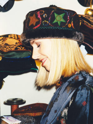 A close up of a woman wearing a brown Rusalka hat with appliqué felt stars on it.