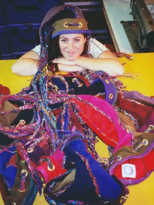 A pile of Squid Toques in front of a women wearing a Squid Toque