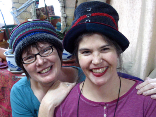 2 women wearing hats, one with glasses has her new Tibetan hat on.