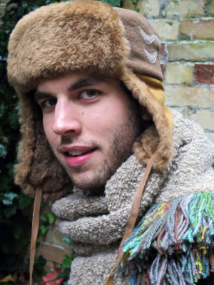 A man wearing a beige wool and shearling ear flap hat