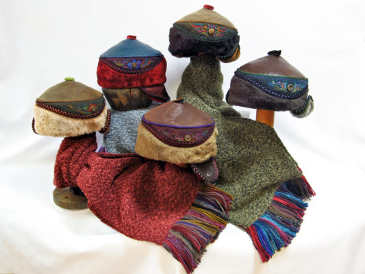 5 Anoushka design hats sitting on top of Gwendolyne's hand fringed boucle knit scarves.