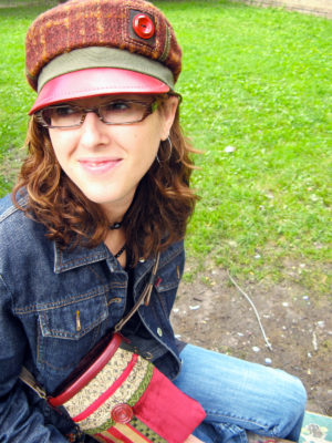 A close up of woman wearing a Abbey Road Cap in colours red and brown sitting on the grass with a Nathaniel shoulder bag