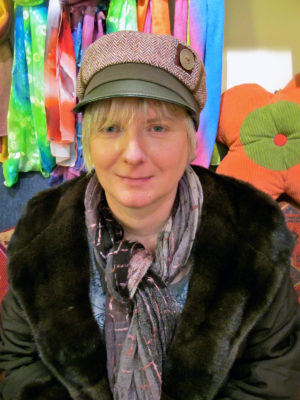 A woman wearing her new olive and red Abbey Road Cap sitting in the shop