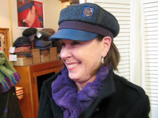 A close up of happy customer wearing her new Abbey Road Cap in blue and purple colours.
