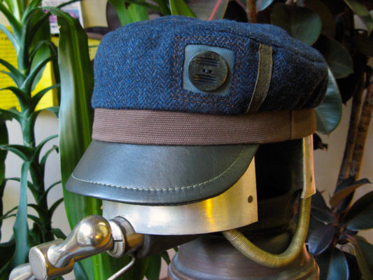 An Abbey Road Cap in navy brown and green on a hat stretcher