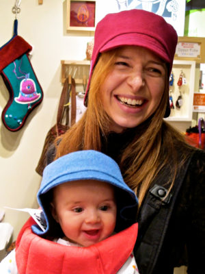 Happy new customer wearing her new pink Amelia Hat with her baby modelling a blue one.