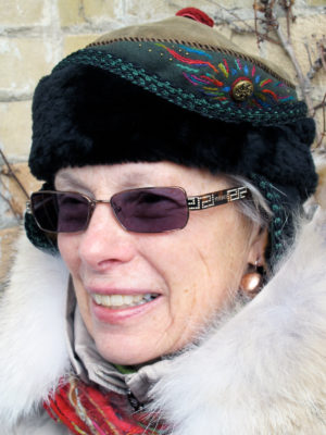 A woman wearing her new black and olive Anoushka hat outside.