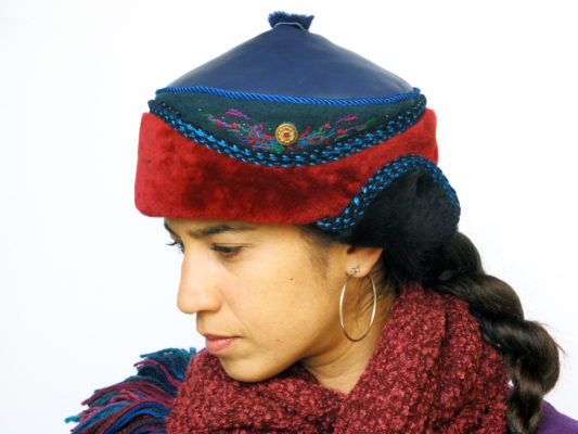 A close up of a woman wearing a red and blue Anoushka Design Hat