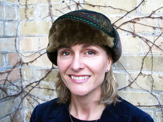 A close up of a woman wearing her new olive green Anoushka Design Hat