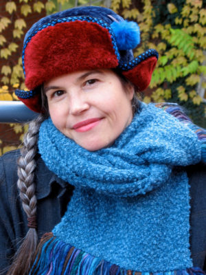A close up of a woman wearing a blue and red Pom Pom Hat
