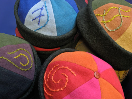 4 colourful Bean Toques in a pile showing off the embroidered motif