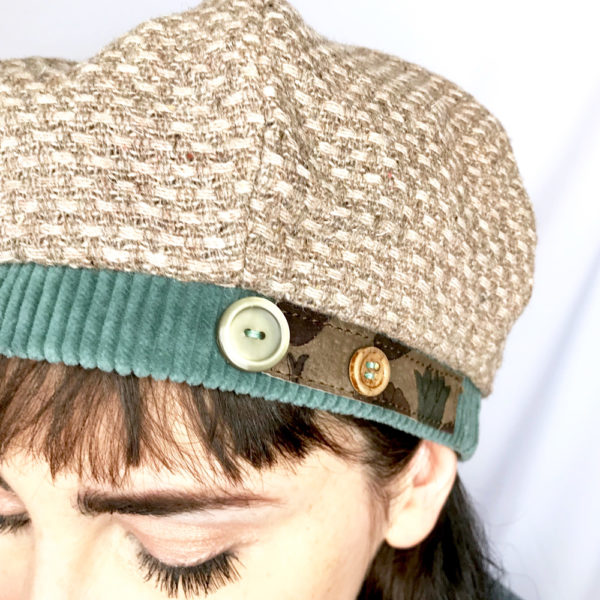 Close up of a Woman wearing a Beige Bella Beret looking downwards.