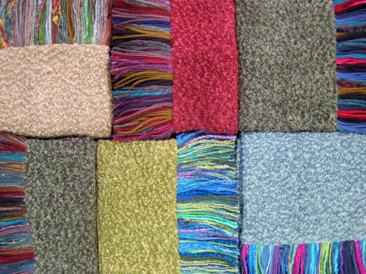 6 Hand Fringed Boucle Knit Scarves laid out in colours red, green, blue, lime and beige