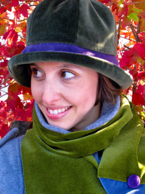 A close up of woman wearing a olive and mauve Chloe Cloche hat set against bush of red leaves