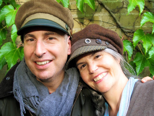 Happy client wearing his new brown Abbey Road cap beside Gwendolyne who's wearing a Donavan cap.