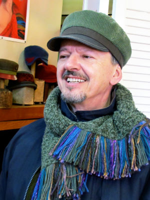 A close up of a man wearing a Cordy Cap in sage green and brown colours with a sage green boucle knit scarf
