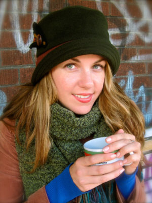 A woman sitting on a bench holding a cup of coffee and wearing a olive Corona Hat.