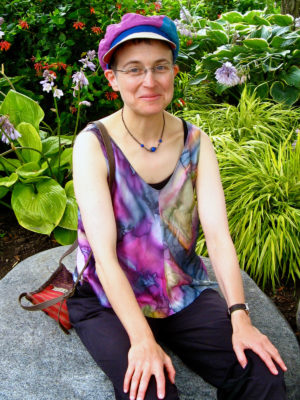 A woman wearing her new Delbert cap sitting down in a garden.