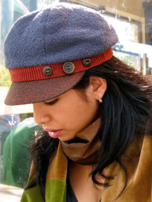 A close up of a woman wearing a grey papaya and brown cap.