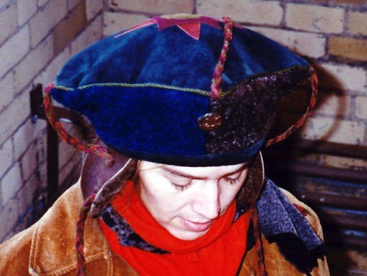 A close up of a woman looking down wearing a blue Theodore Hat