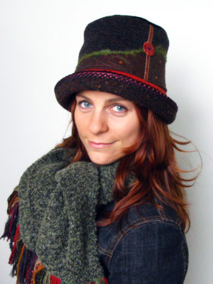 A close up of woman wearing a Estonian Hat in the colours brown and orange