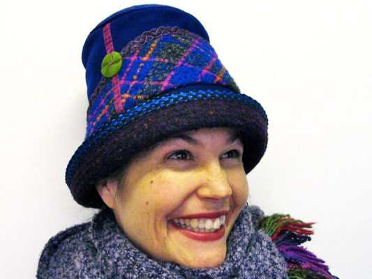 A close up of woman wearing a Estonian Hat in the colours blue and purple