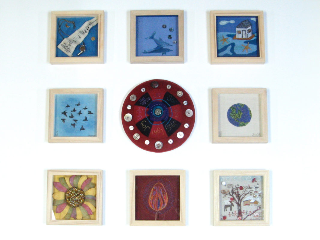 framed embroidery works around a large pin cushion