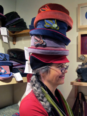 Gwendolyne wearing 4 hats stacked on top of one another at the One of a Kind show