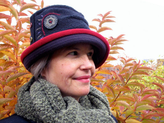 A close up of woman wearing a black and red Harvest Moon hat design set against a Fall leaf background