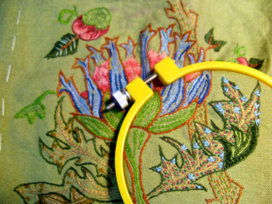 Yellow embroidery hoop close up of leaves and flower bloom