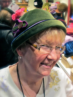 Close up of a happy new customer wearing her new olive LaBijou hat.