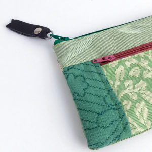 Image close up of the front side of the wallet showing the patchwork tapestry and the zipper fobs