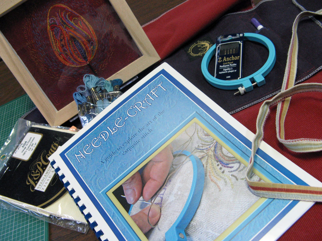 Image of the Atelier Gwendolyne Needle Craft booklet embroidery hoop, embroidery floss and a Fire artwork framed