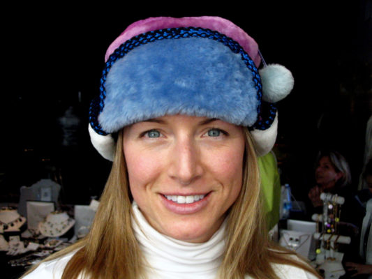 A close up of a woman wearing a light blue, hot pink and white Pom Pom Hat