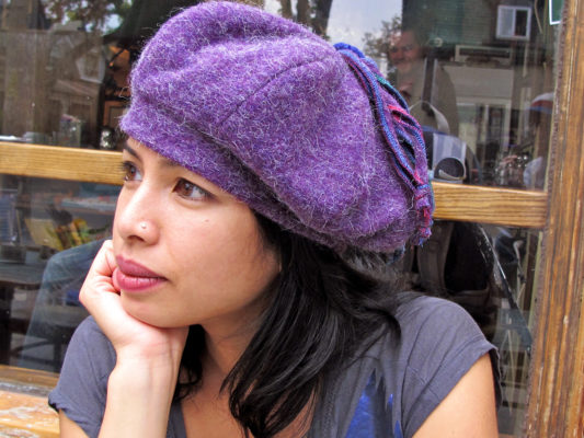 A close up of a woman wearing a The Purple Pumpkin Beret