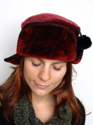 A close up of a woman wearing a red and black Pom Pom Hat