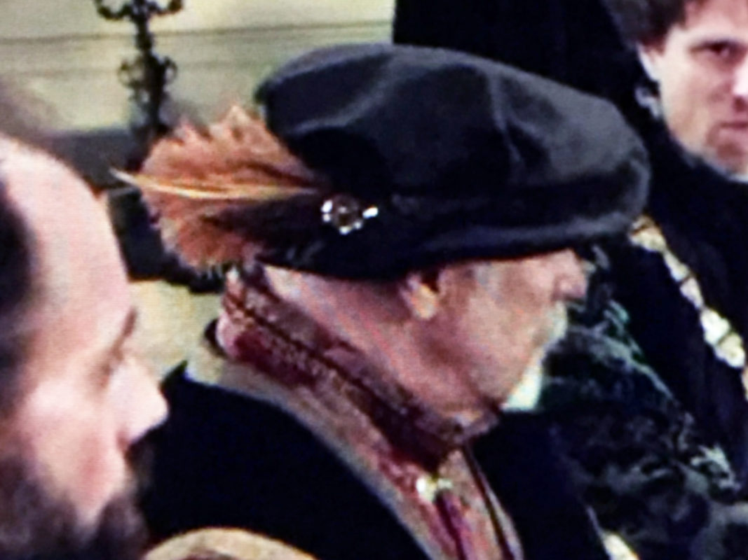 Profile shot of a white bearded man wearing a black Tudor hat.
