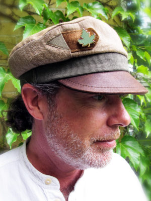 A close up of customer wearing his new custom ordered Robin Cap with a leather peak and a leaf brooch