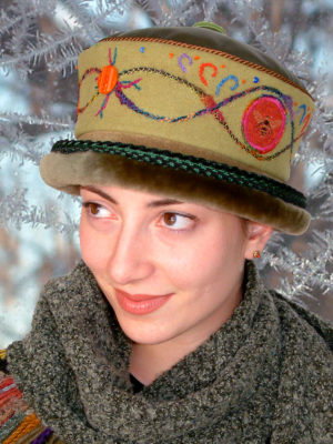 A close up of woman wearing a soft lime Rusalka Hat with a olive coloured fur rim