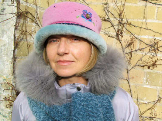 A close up of woman wearing a soft pink Rusalka Hat with a sea foam blue coloured fur rim
