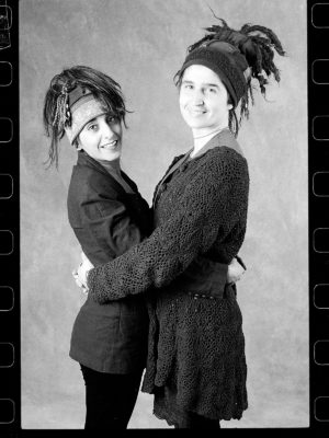 An early black and white photo of two friends modelling Gwendolyne Hats wool Twirl String Toque.